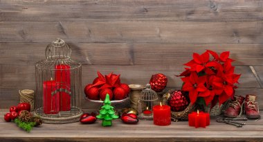 Christmas decoration with burning candles red flowers