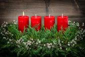 Fotografie Advent Dekoration mit vier roten brennenden Kerzen vintage