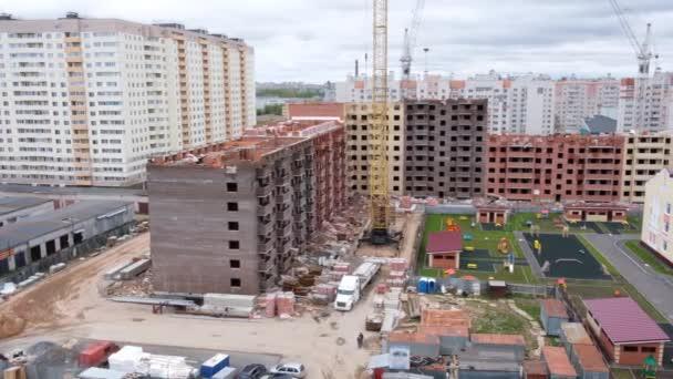 Panoramatický pohled shora na budovu ve výstavbě a jeřáby