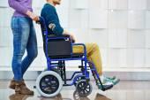 muž na invalidním vozíku s pečovatelem