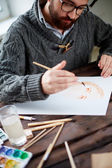 man painting with watercolor