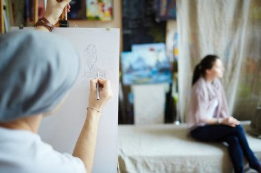 Student drawing a woman in studio