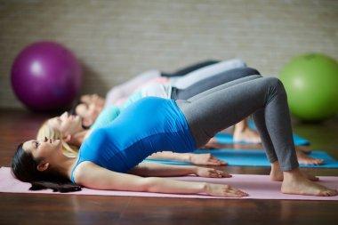 pregnant women exercising on mats