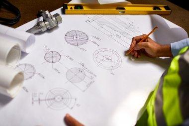 Engineer drawing sketch of machine part