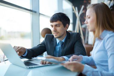 Employees discussing data in laptop at meeting