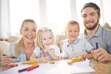 Happy family drawing together at home