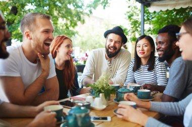 Joyful teens having talk by tea