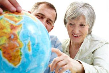 Happy senior couple looking at globe