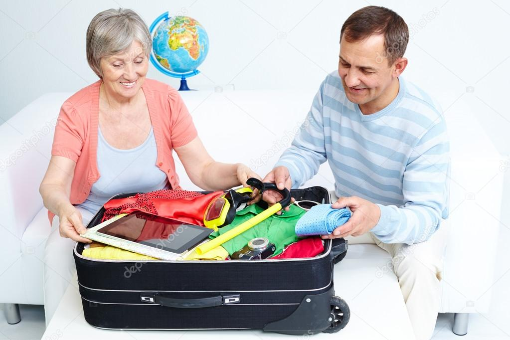 happy senior couple packing suitcase