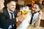 Fotografie Businessmen celebrating and toasting with beer