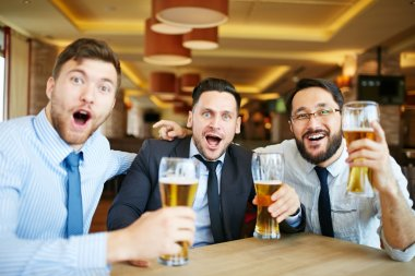 Excited men drinking beer
