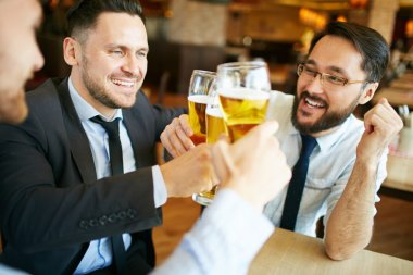 Businessmen celebrating and toasting with beer