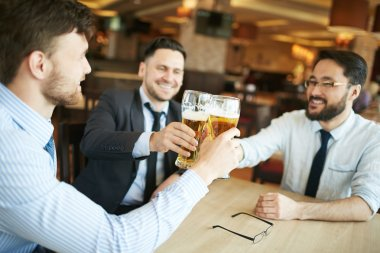 Businessmen celebrating with glasses of beer