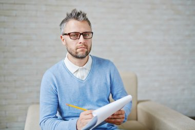 Serious psychologist with document