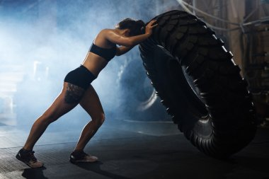 Strong woman flipping tyre