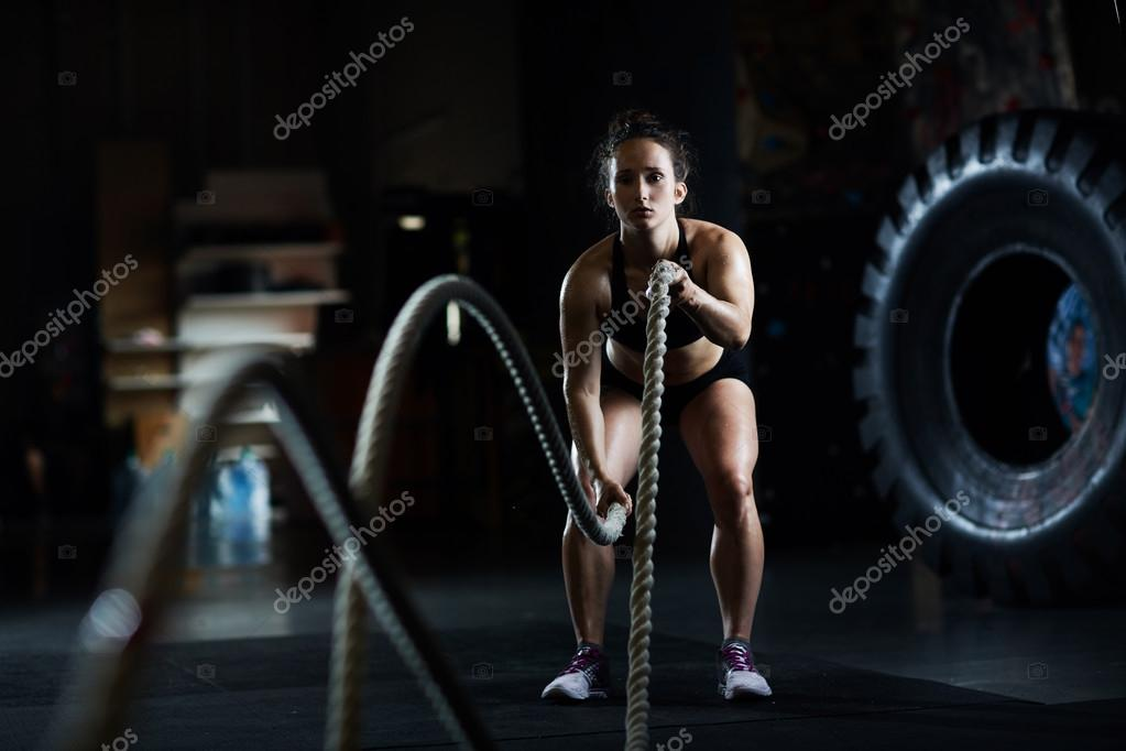 woman practicing exercise with ropes