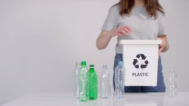 Midsection footage of female holding white container for sorting waste filling it with empty plastic water bottles