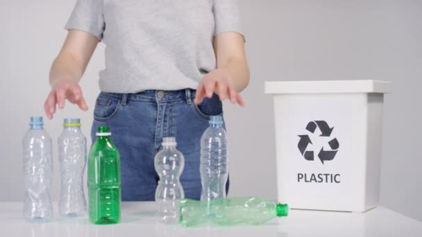 Midsection footage of unrecognizable female ecology activist sorting plastic bottles in container for recycling
