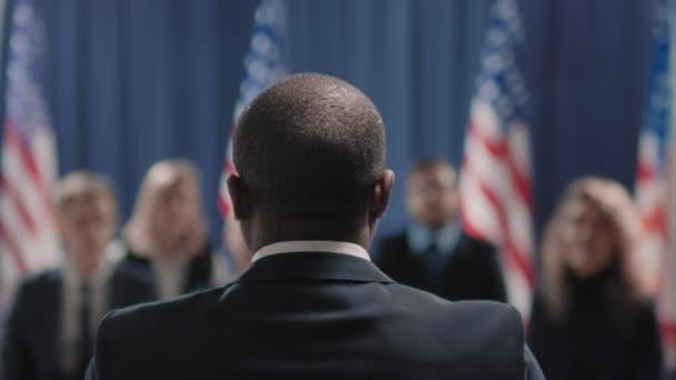 Aufnahmen von hinten, auf denen zu sehen ist, wie ein nicht wiedererkennender afroamerikanischer Politiker seine Rede auf der Pressekonferenz beendet, Journalisten aufstehen und applaudieren
