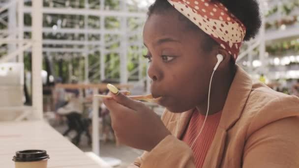 Seitenansicht der schönen afroamerikanischen Frau mit Kopfhörern, die am Tisch im Außenhof des Cafés sitzt und per Videoanruf plaudert, während sie in der Mittagspause Eis genießt