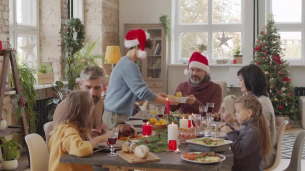 Medium shot of happy family of seven sitting together at dinner table and eating tasty dishes on Christmas day
