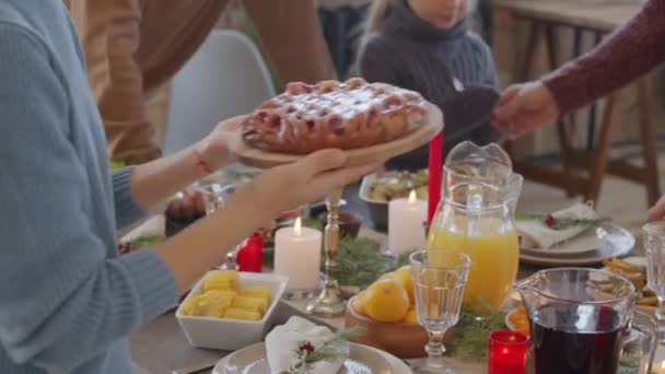 PAN mid-section of female hands giving tasty pie on wooden plate to unrecognizable woman while helping set dinner table on Christmas