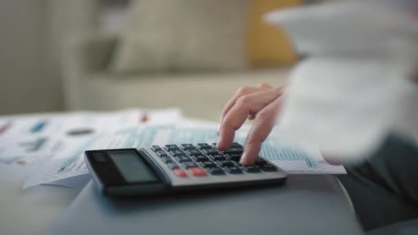 Closeup of unrecognizable female hands counting bills and taxes on calculator analyzing incomes and expenses planning budget