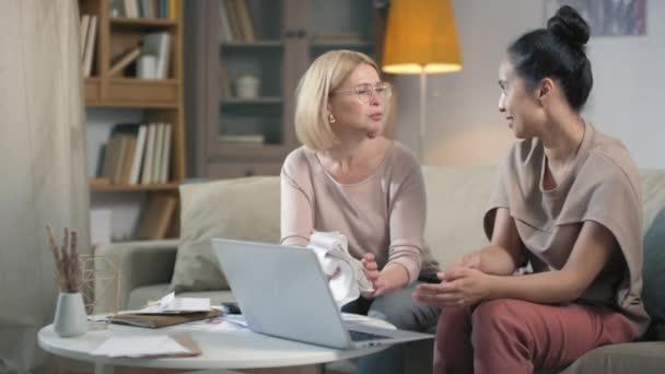 Kaukasische Frau mittleren Alters lernt Finanzbuchhaltung mit Hilfe einer jüngeren Tochter, die erklärt, wie man Rechnungen bezahlt und das Budget online mit Laptop im Wohnzimmer plant