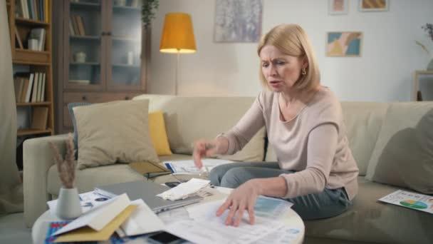 Stres středního věku žena při pohledu přes hromady papírů na chaotický stůl při analýze financí stále rozrušený a frustrovaný