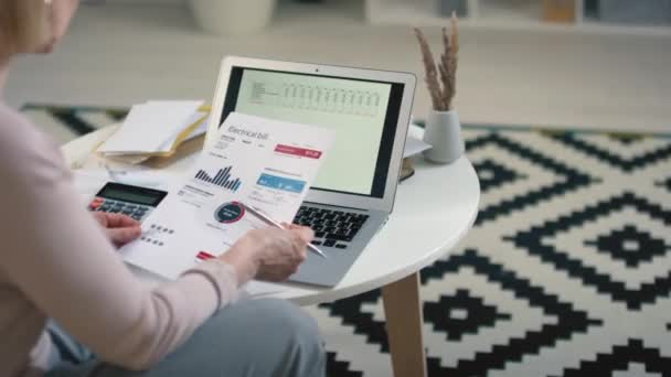 Back-view footage of caucasian woman sitting in front of laptop with opened planning spreadsheet managing budget according to monthly mandatory expenses looking at printed charts and diagrams