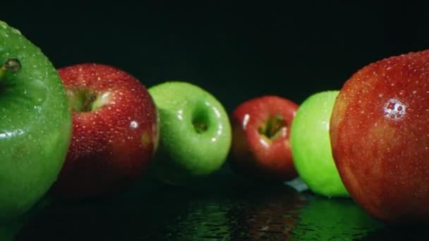 Zoom in macro closeup of colorful ripe apples freshly picked and washed lying on black surface