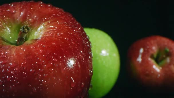 Macro closeup of shiny water pouring from above on ripe homegrown red apple with other fruit on dark background