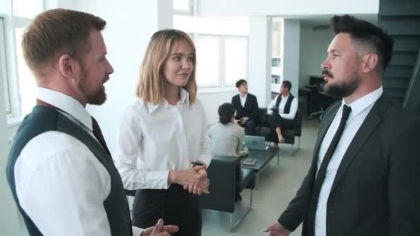 Ruční oblouk záběr mladé ženy a jejích mužských kolegů stojí spolu a mluví o něčem