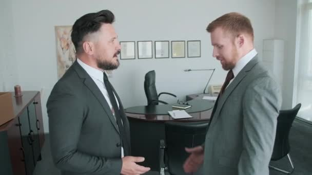 Side view shot of two handsome office workers in formalwear talking and shaking hands after making agreement