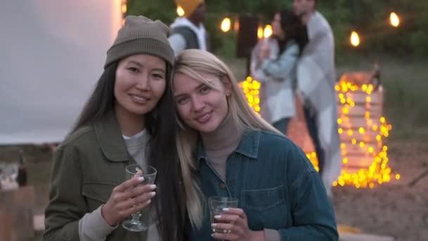Nahaufnahme von hübschen blonden und brünetten Freundinnen, die bei einer Open-Air-Party lächelnd in die Kamera schauen, während Freunde im Hintergrund neben Projektor und DJ-Deck chillen, dekoriert mit gemütlichen Lichterketten