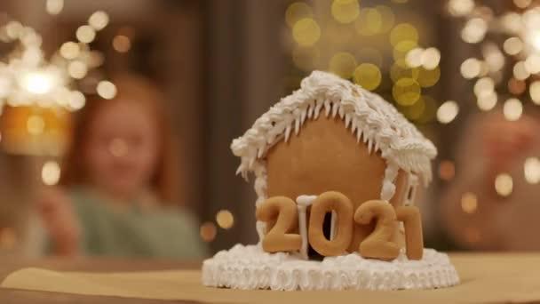 Közelkép a díszített mézeskalács ház és elmosódott sziluettek anya és lánya égő csillagszórók a háttérben ünneplő karácsony