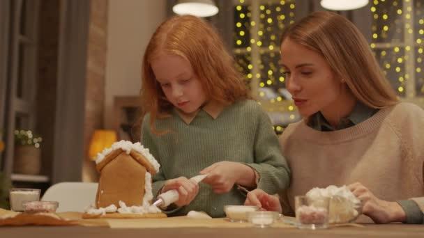Střední záběr krásné holčičky s taškou na pečivo v rukou sedí u vánočního stolku vedle její milující maminka zdobení domácí perník dům spolu v jasném útulném obývacím pokoji