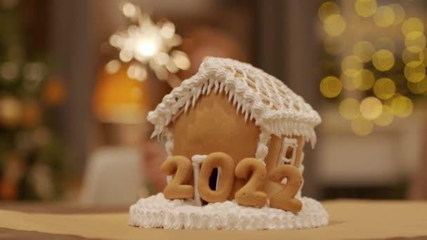 Közelkép a nagy díszített mézeskalács ház a kislány kezében fényes csillagszórók a háttérben karácsony este