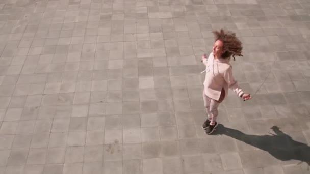 Filmmaterial von oben: fitte Kaukasierin springt beim morgendlichen Outdoor-Training mit Springseil und verbrennt Kalorien