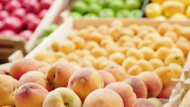 Kézzel tartott közeli nyomon követése egy csomó friss őszibarack feküdt ládában gyümölcsös stand a piacon vagy szupermarketben