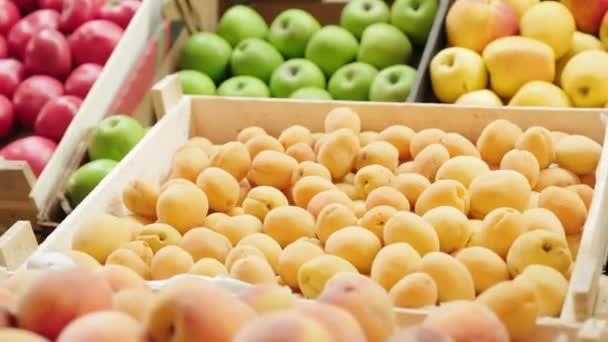 Az érett kajszibarack, nektarin és alma közvetlen felkutatása ládákban a zöldségesnél a szupermarketben