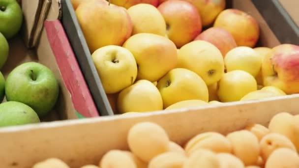Kézi nyomkövetés friss kajszibarackkal, őszibarackkal és almával, ládákban a szupermarketben vagy a piacon lévő gyümölcsstandon