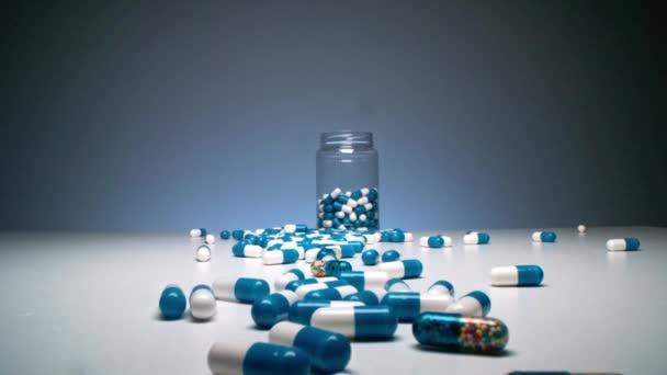 Zoom-Makroaufnahmen von halb leeren Glasflaschen mit bunten Kapselpillen, die auf klarer Oberfläche vor blauem Hintergrund verschüttet wurden