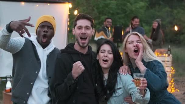 Multi-etnikai barátok csoportjának portréja, akik nagy örömüket és örömüket lelik a kamerában, míg mások a konzol és DJ keverése mellett táncolnak a háttérben, nyári partit rendezve