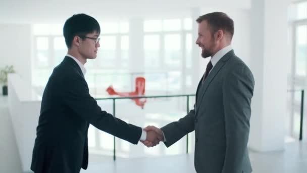 Boční pohled střední záběr záběry dvou mladých dospělých podnikatelů pozdravuje navzájem s potřesením rukou a mluví o něčem