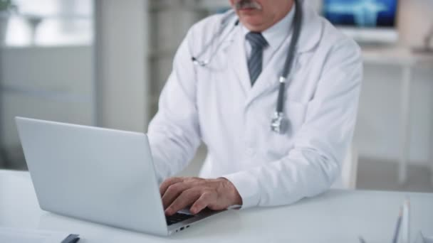 Portrait shot footage of cheerful aged medical worker sitting at desk typing something on computer then looking at camera