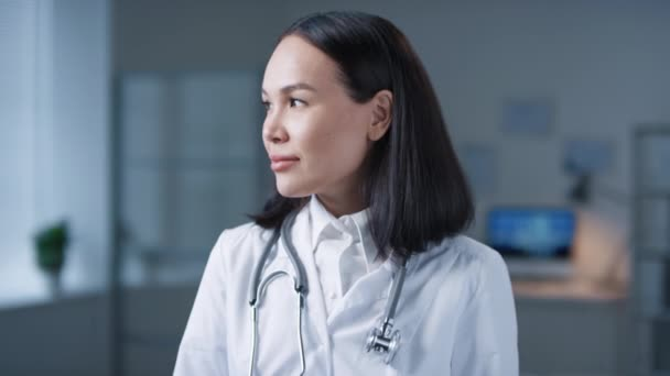 Medium close-up portrait shot footage of attractive Asian woman working in hospital wearing white coat and stethoscope around neck looking away then at camera
