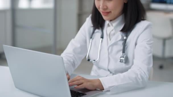 Portrét krásné mladé dospělé asijské ženy v bílém plášti a stetoskop kolem krku pracuje na notebooku a pak se usmívá na kameru