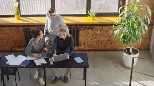 Z výše uvedených záběrů mužského režiséra pomáhá kancelářským pracovníkům s chystaným obchodním projektem dává rady při pohledu na obrazovku notebooku spolu