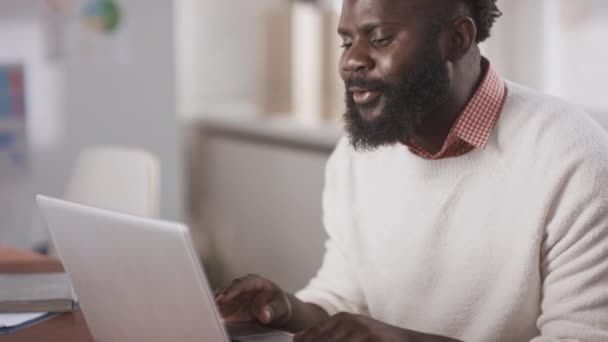 Medium close-up portrait shot footage of young adult African American man with beard on face sitting in front of laptop taking part in online meeting